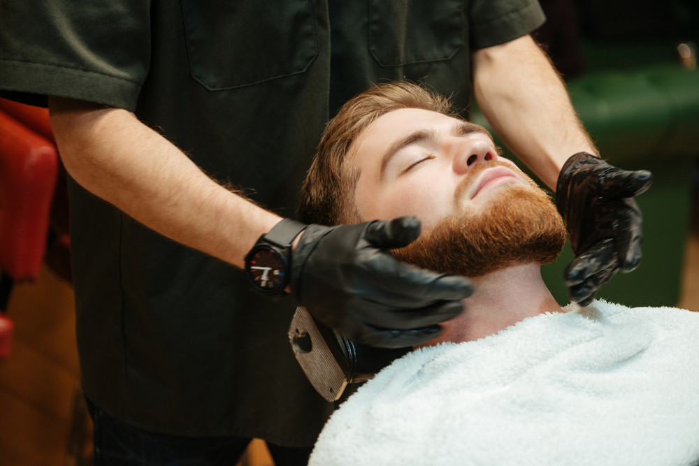 Photo of bearded man getting beard shaving by hairdresser while lies in chair at barbershop.