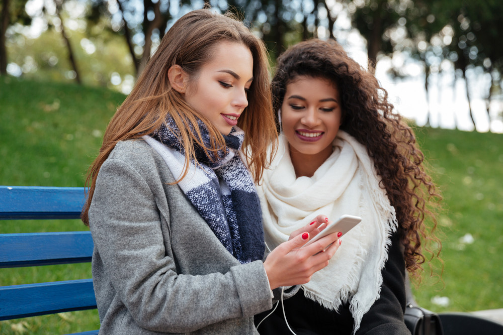 Photo of beautiful young women sitting on a bench and listening music together on earphones. Horizontal shot. Looking at phone. With grass on background.