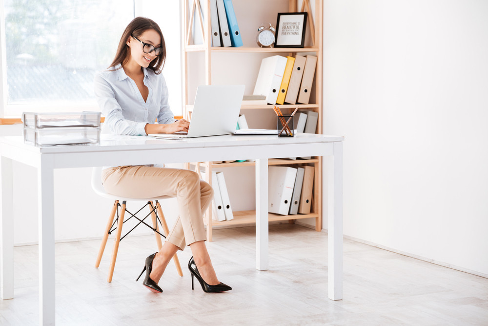 Photo of businesswoman dressed in white shirt and wearing glasses sitting in her office and using laptop. Looking aside.