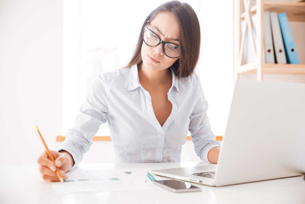 Photo of businesswoman dressed in white shirt sitting in her office and writing notes.