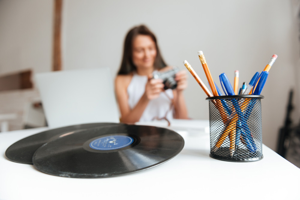 Photo of casual woman working on a laptop sitting on the chair in the house while holding camera. Focus on table with vinyl record and pencils.