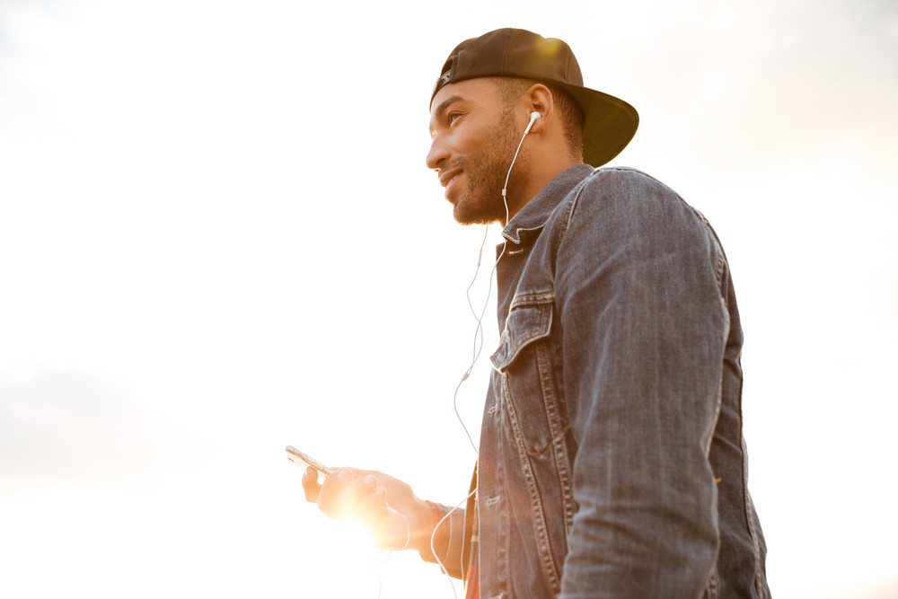 Photo of cheerful african young man wearing cap walking on the beach and chatting by his phone while listening music with earphones.