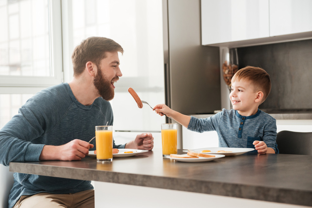 Photo of cheerful bearded father dressed in blue sweater eating at kitchen with his little son