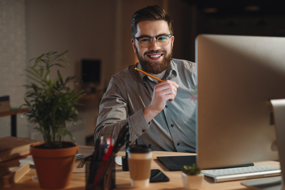 Photo of cheerful bearded web designer dressed in shirt working late at night and looking at camera while holding pen in hand.