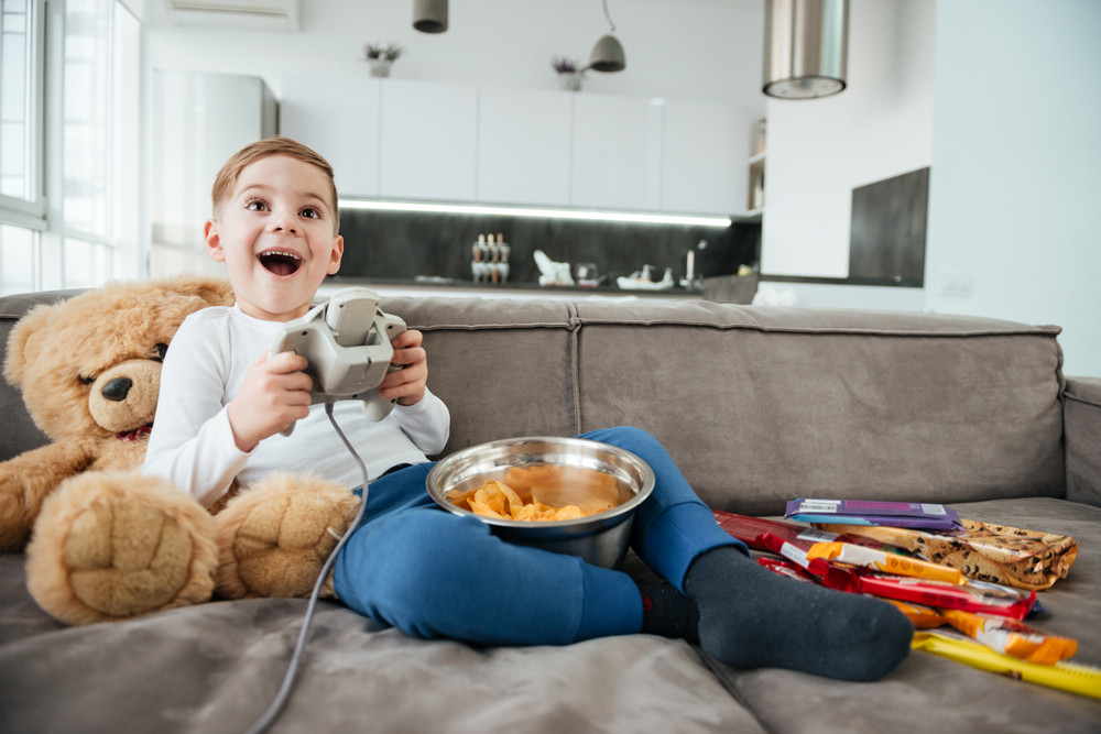 Photo of cheerful boy on sofa with teddy bear at home playing games by console while eating chips. Holding joystick.