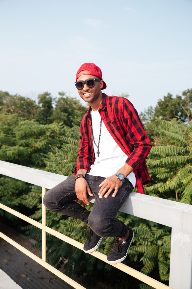 Photo of cheerful dark skinned young guy wearing sunglasses sitting against nature background