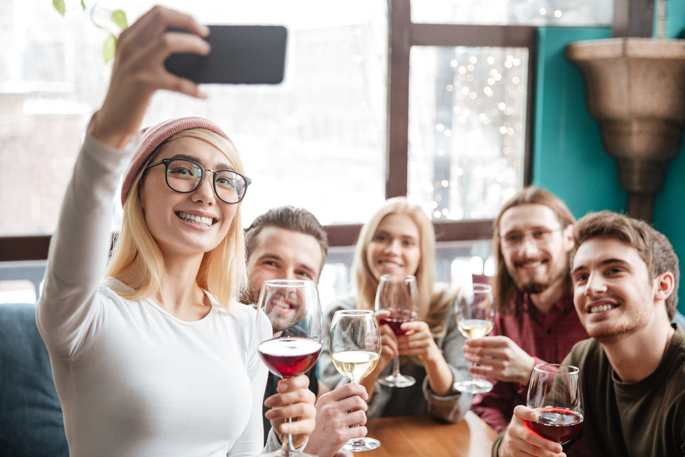 Photo of cheerful friends sitting in cafe and drinking alcohol and make a selfie by phone.