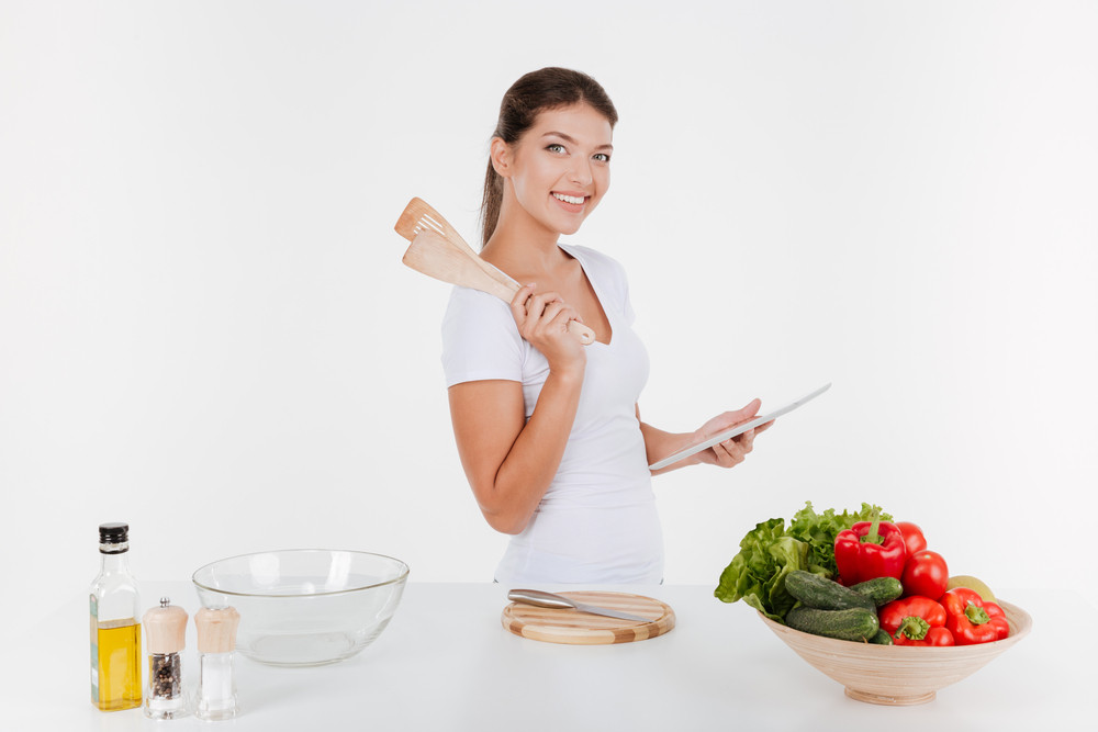Photo of cheerful woman cooking with vegetables. Isolated on white background.