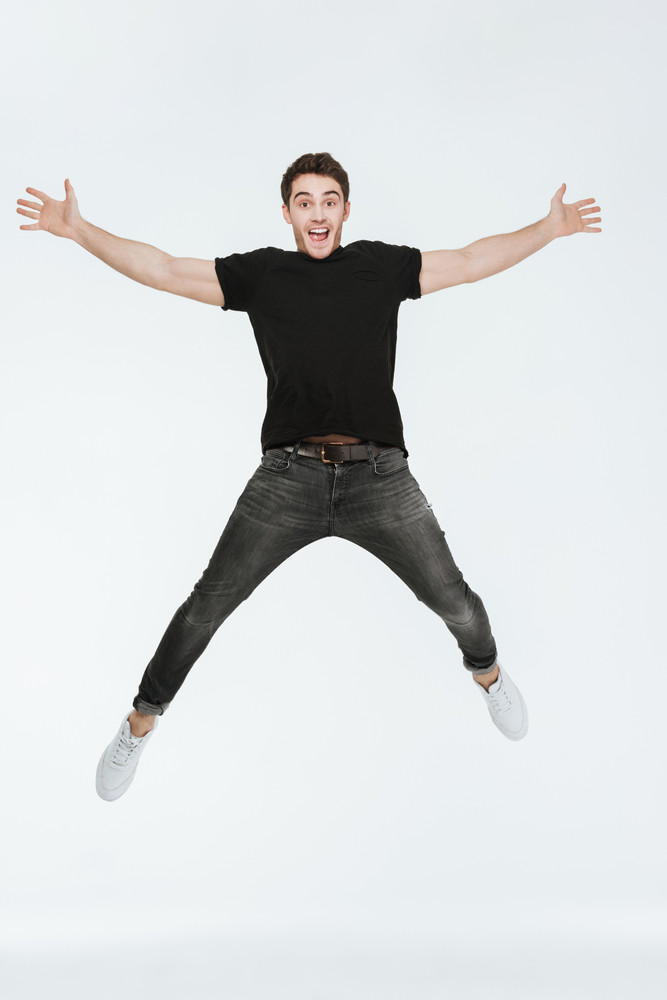 Photo of cheerful young man dressed in black t-shirt jumping over white background looking at camera.
