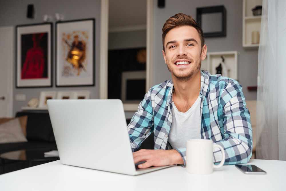 Photo of cheerful young man dressed in shirt in a cage print sitting in home and using laptop computer. Looking at camera while drinking tea.