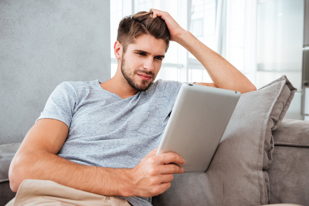 Photo of cheerful young man looking at tablet while sitting on sofa