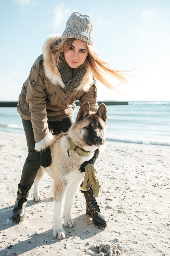 Photo of cheerful young woman walks in winter beach with dog on a leash.