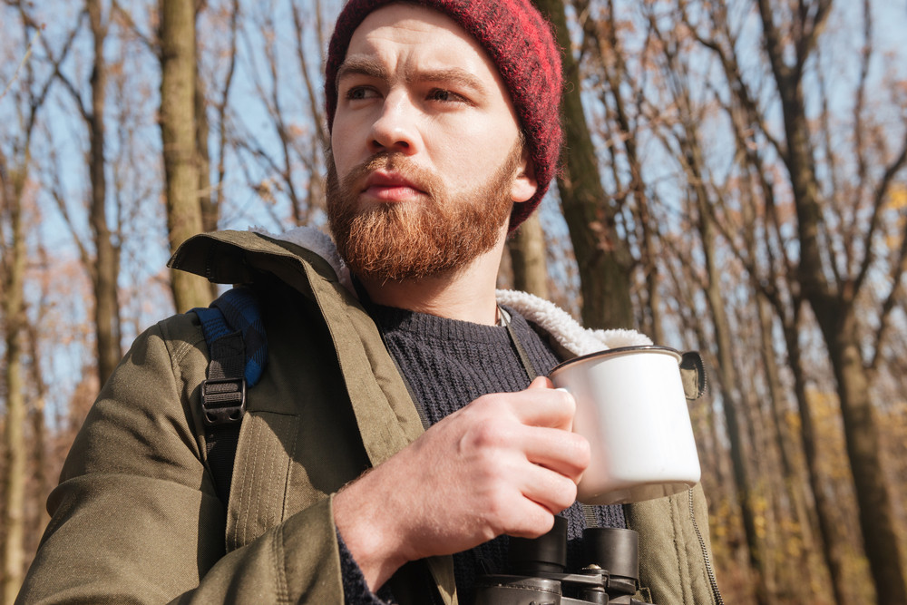 Photo of concentrated bearded man wearing hat holding cup of tea in hands standing in the forest and drinking.
