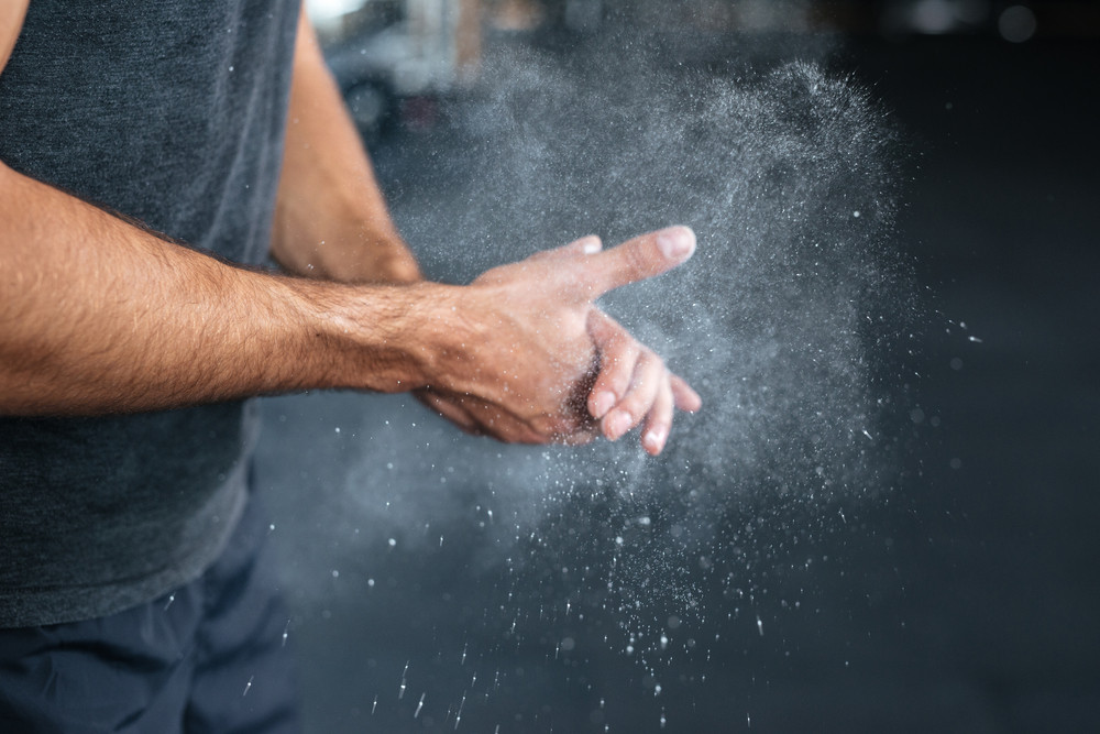 Photo of fitness hands. rubbing hands with chalk