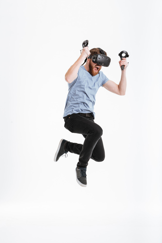 Photo of funny bearded man wearing virtual reality device jumping over white background.