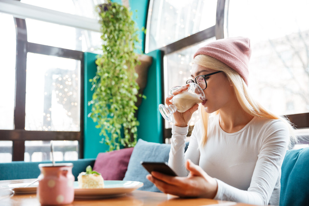Photo of gorgeous young lady wearing hat and glasses using cellphone while sitting in cafe and drinking coffee.