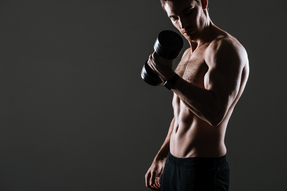 Photo of handsome athlete standing with dumbbell in gym over grey background.