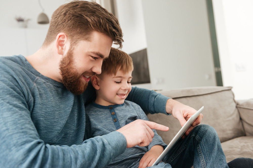 Photo of handsome father using tablet computer with his little cute son.