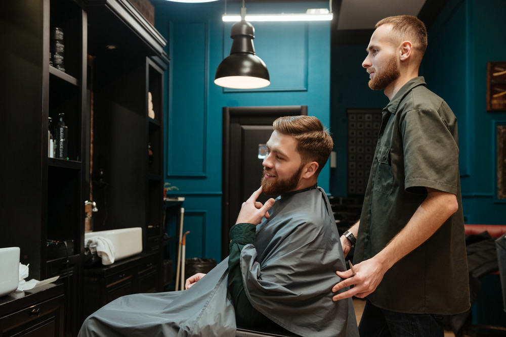 Photo of handsome man getting haircut by hairdresser while sitting in chair. Look at mirror.