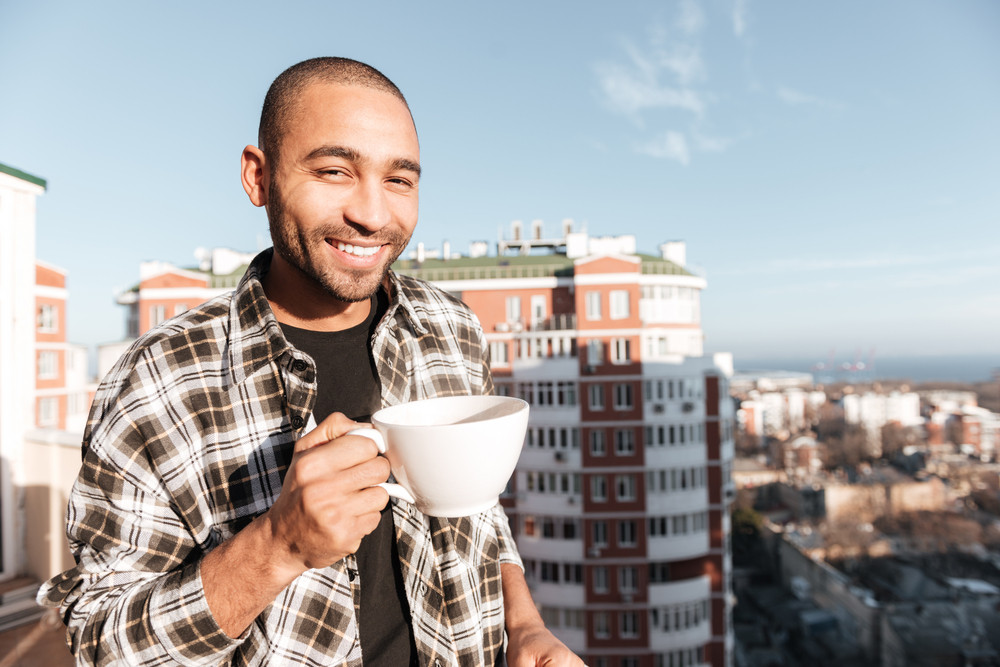 Photo of handsome young african man drinking coffee while standing on roof. Look at camera.