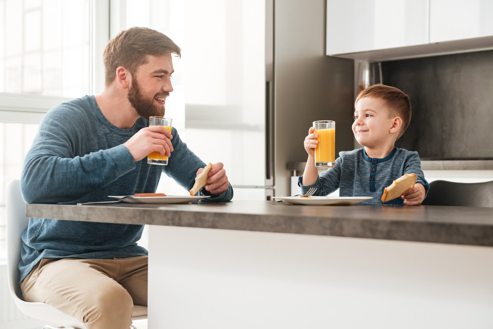 Photo of handsome young father dressed in blue sweater eating at kitchen with his little son
