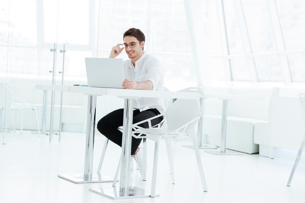 Photo of handsome young man dressed in white shirt using laptop computer. Look at laptop.