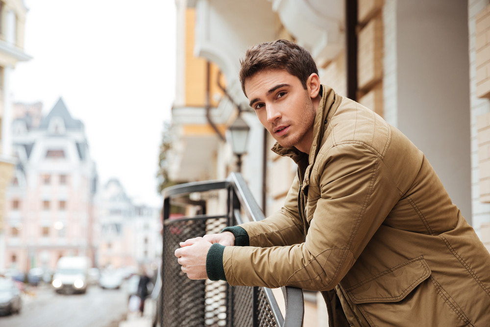 Photo of handsome young man walking on the street and looking at camera.