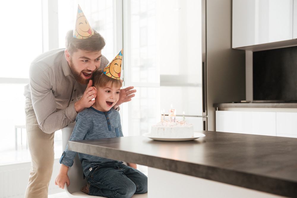 Photo of happy bearded young father in the kitchen with his birthday little son stop to covering his eyes.