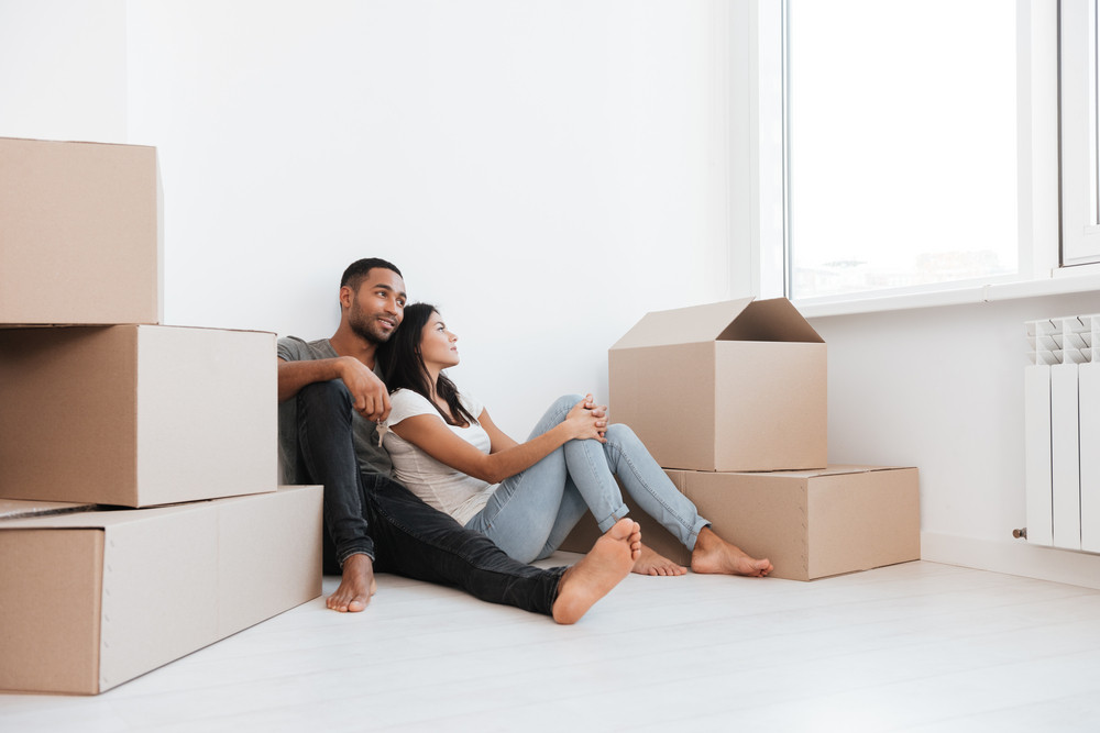 Photo of happy couple sitting with unpacked boxes. Man holding key. Looking aside.