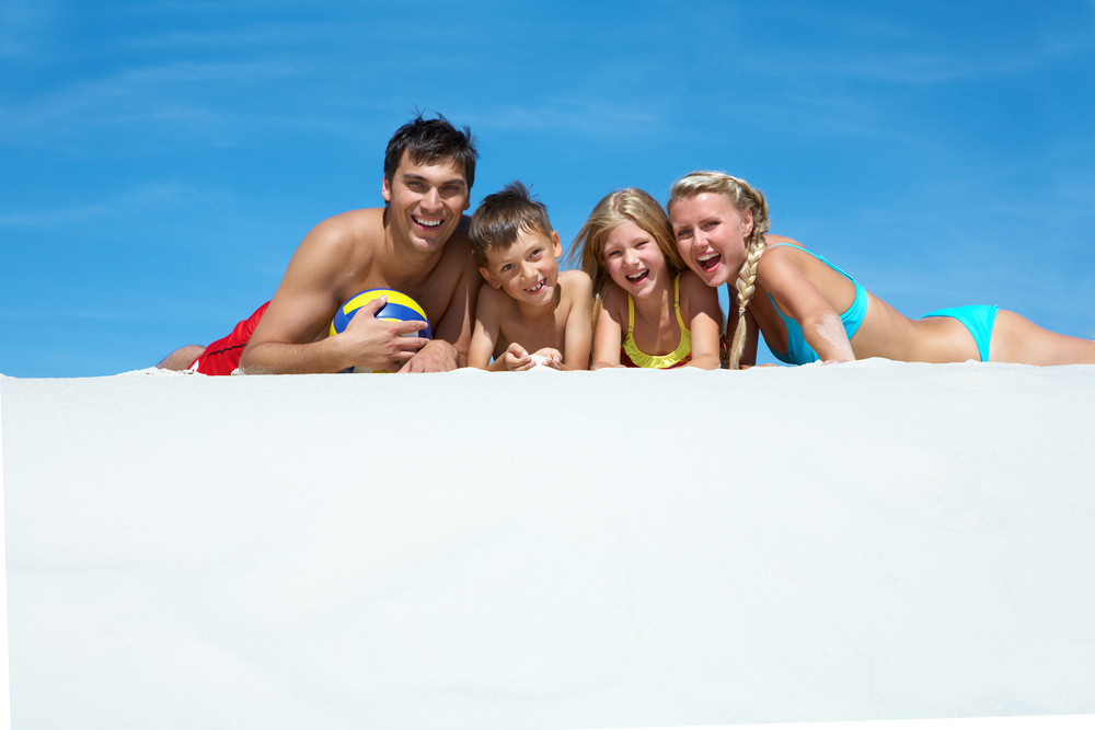 Photo of happy family lying on sand on summer vacation