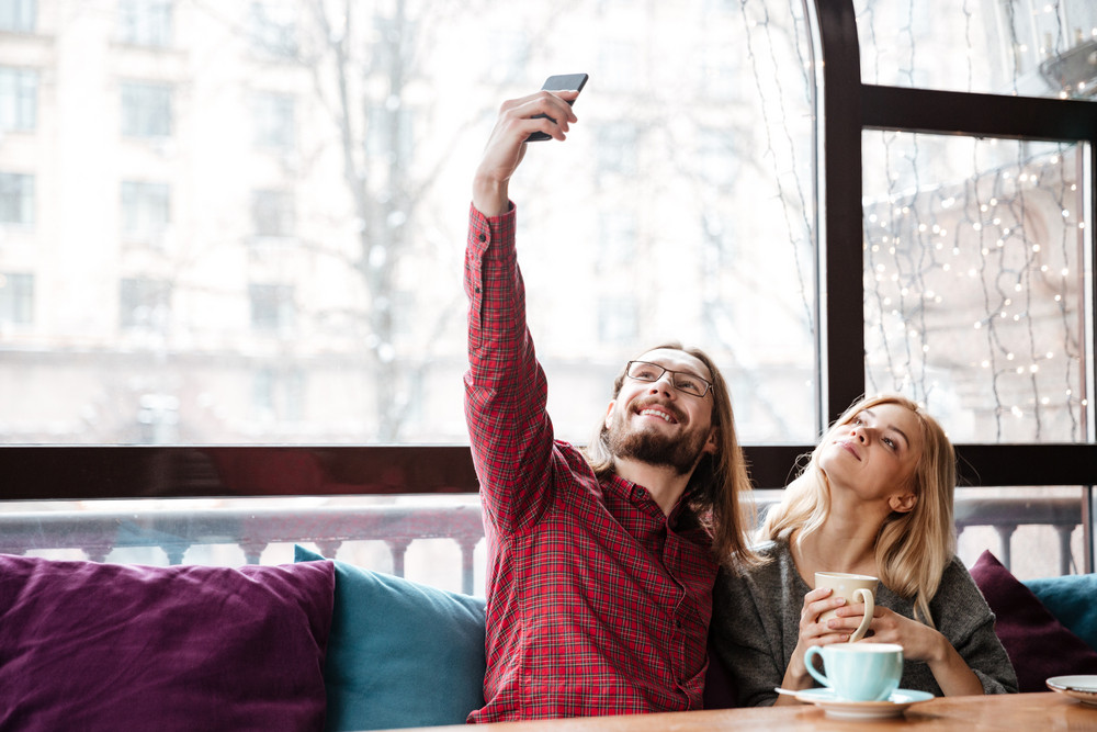 Photo of happy loving couple sitting in cafe and talking while drinking coffee and make a selfie.