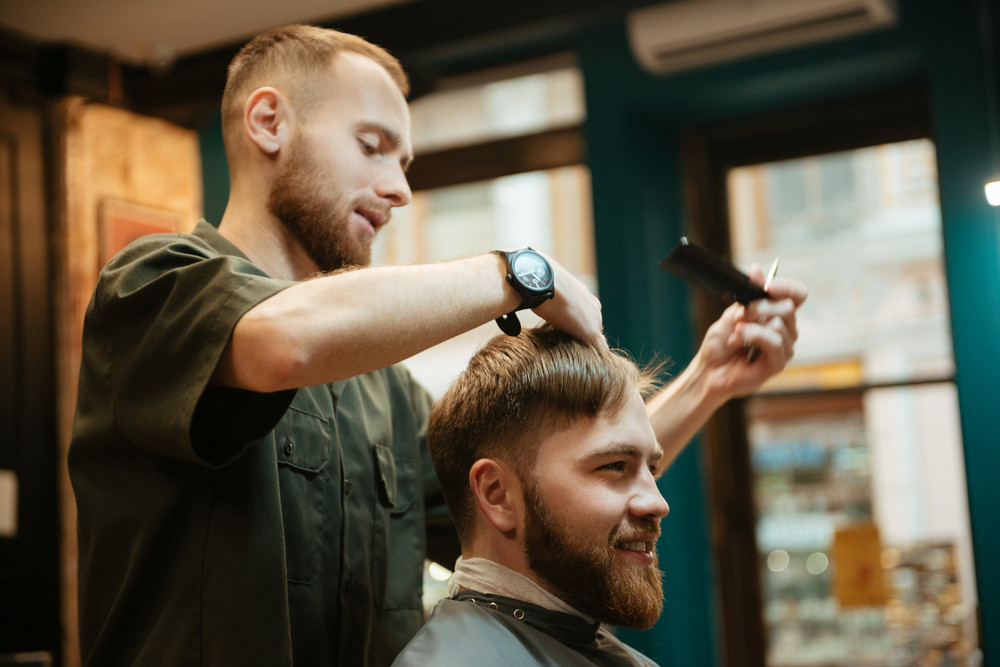 Photo of happy man getting haircut by hairdresser with scissors while sitting in chair. Look aside.