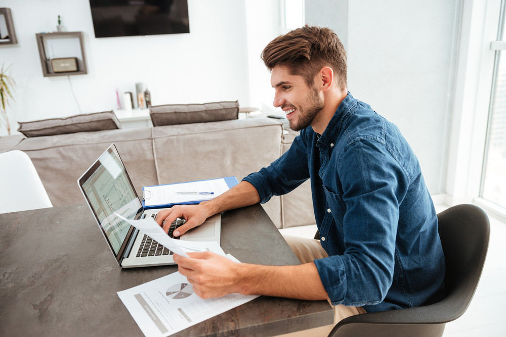 Photo of happy man using laptop and sitting at the table while looking at the papers.
