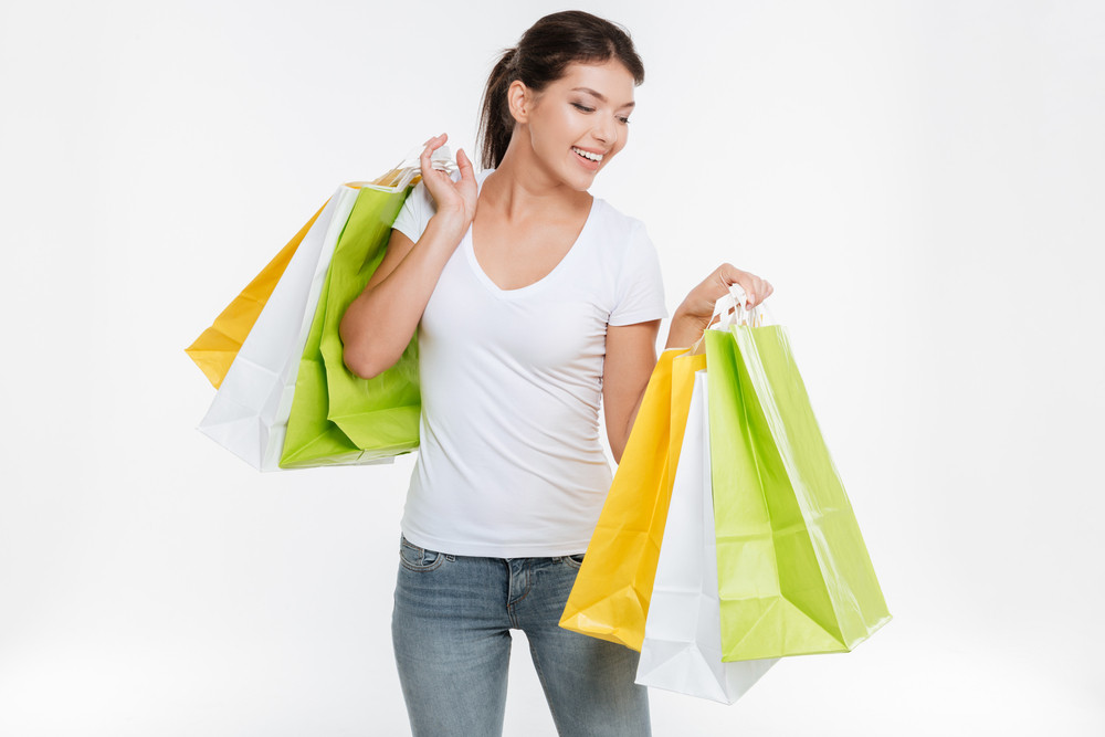 Photo of happy woman holding purchasings after shopping. Isolated over white background.