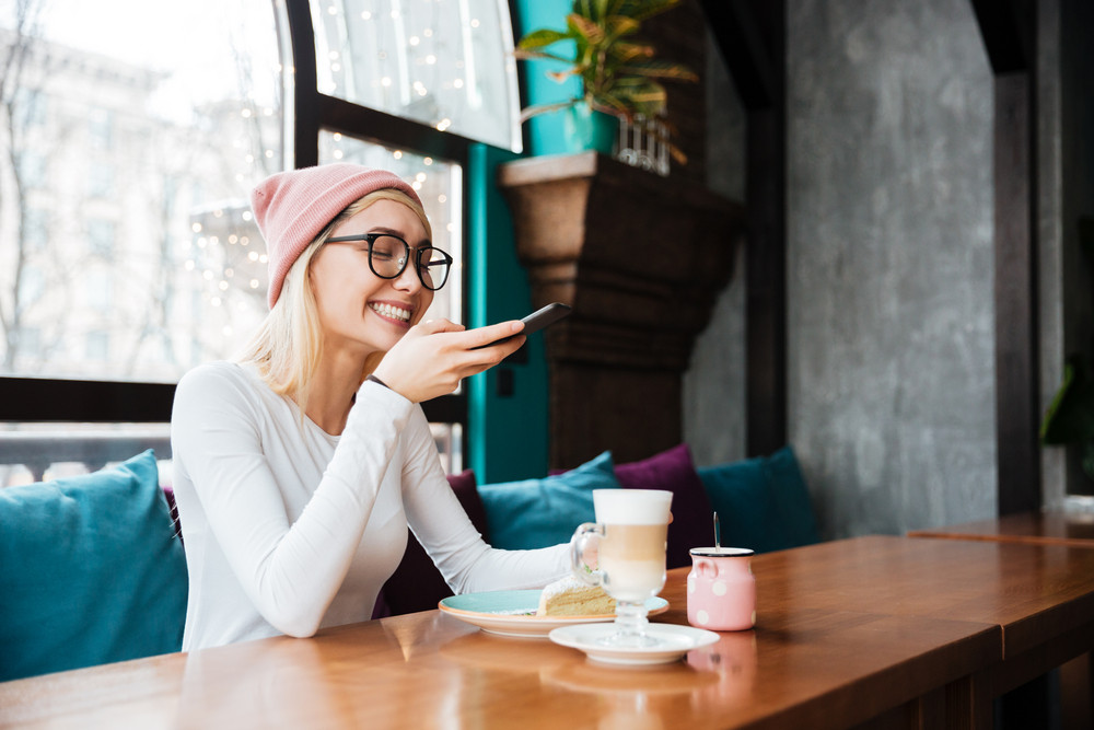 Photo of happy young lady wearing hat and glasses make photo of cake and coffee by phone while sitting in cafe.
