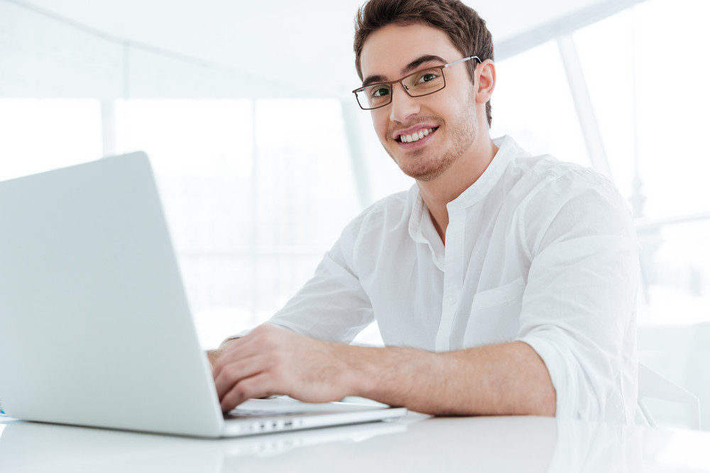 Photo of happy young man dressed in white shirt using laptop computer. Look at camera.