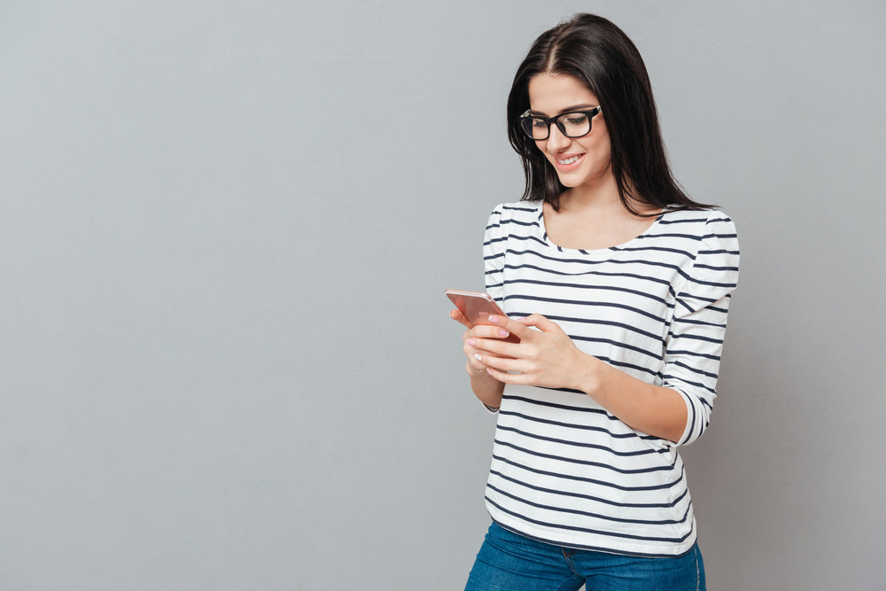 Photo of happy young woman wearing eyeglasses chatting by phone over grey background. Look at phone.