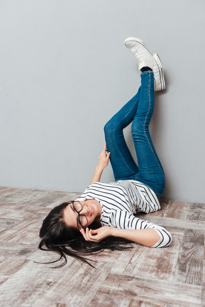 Photo of happy young woman wearing eyeglasses lies on floor over grey background. Look at camera.