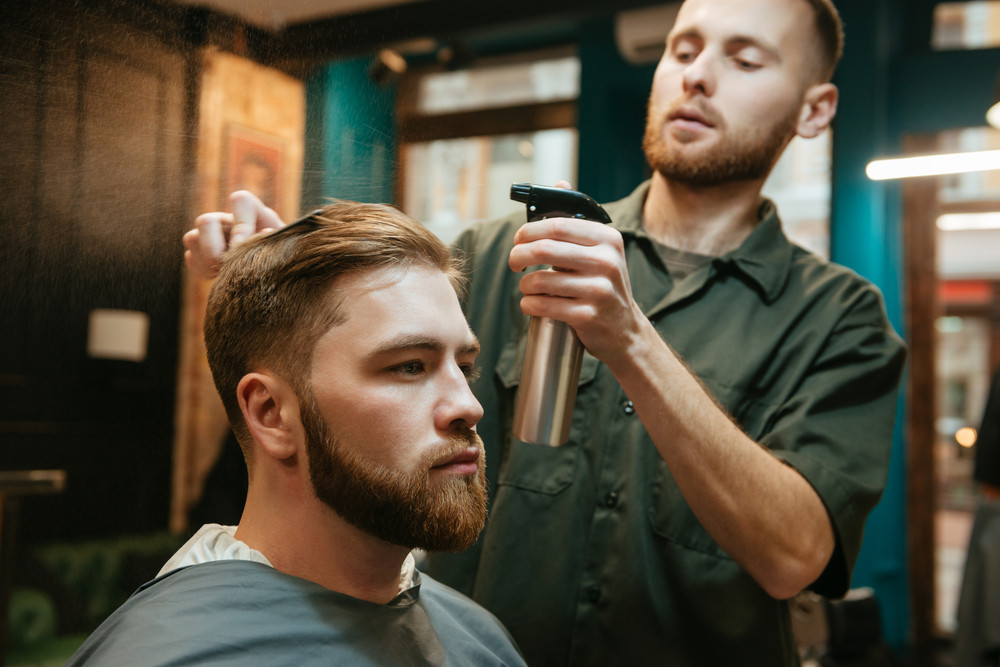 Photo of hipster man getting haircut by hairdresser while sitting in chair.