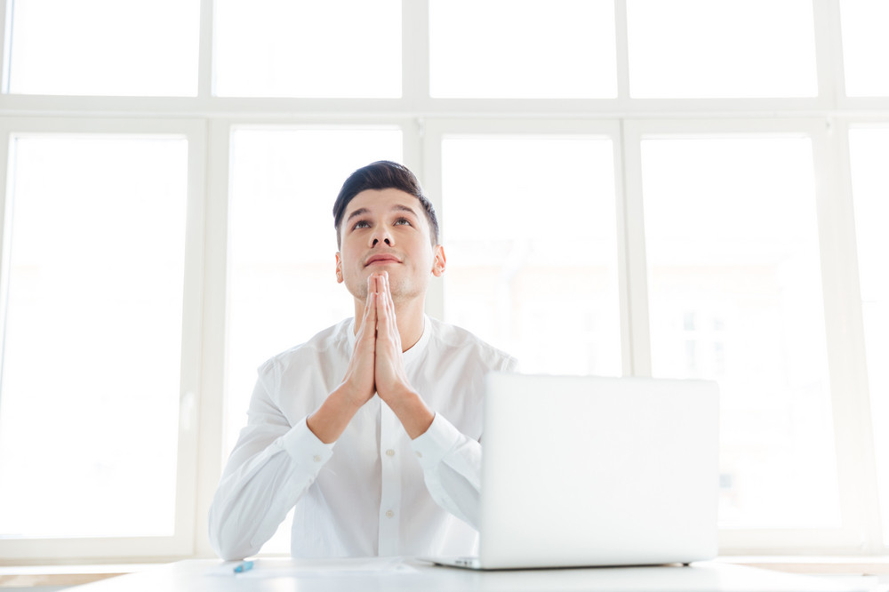 Photo of hopeful man dressed in white shirt using laptop computer prays. Coworking.