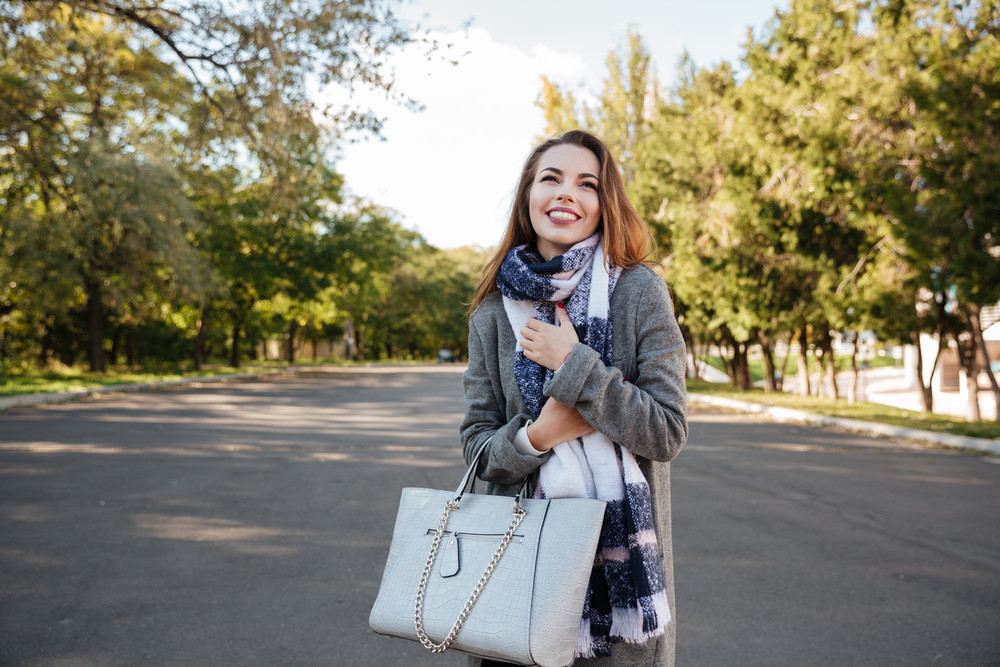Photo of incredible happy lady smiling over nature background and holding bag. Look aside.