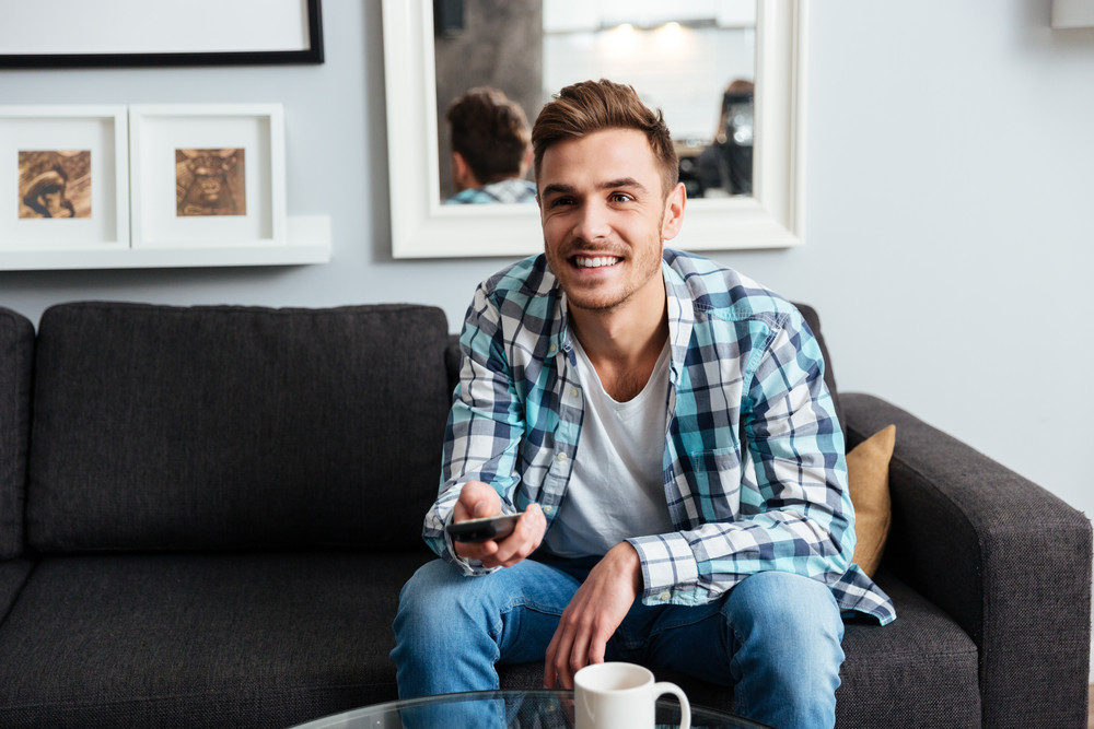 Photo of joyful young bristle man dressed in shirt in a cage print sitting on sofa in home and holding remote control while watching TV.