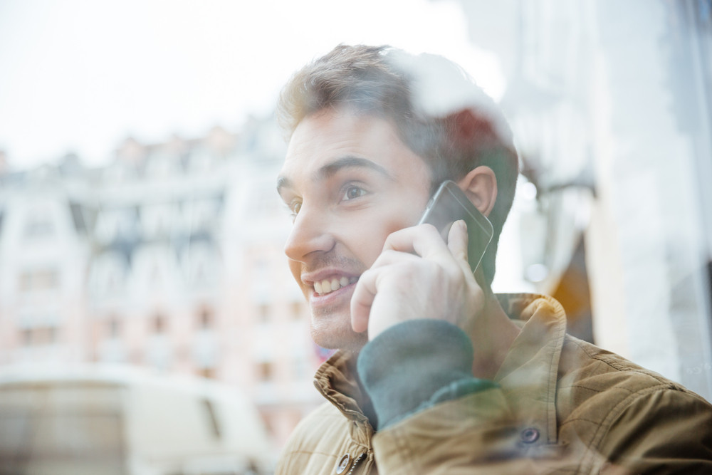 Photo of joyful young man walking on the street and looking aside while talking by his phone.