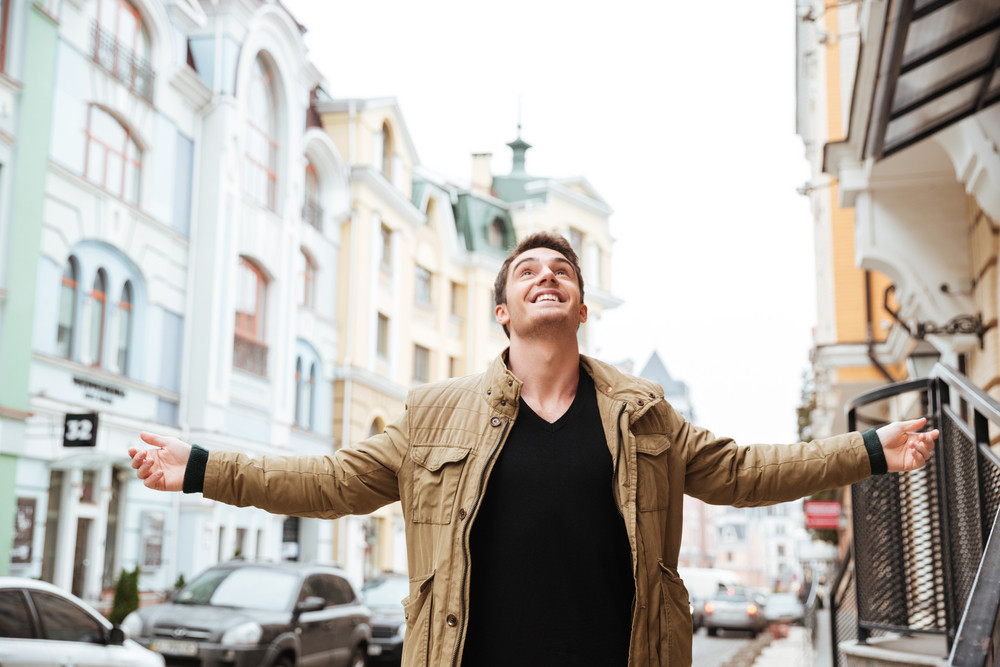 Photo of joyful young man walking on the street and looking up to sky.