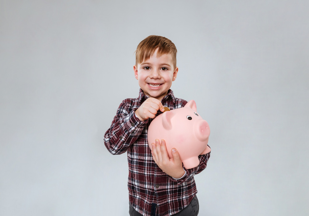 Photo of little cheerful child standing over grey background holding pink pig moneybox. Look at camera.