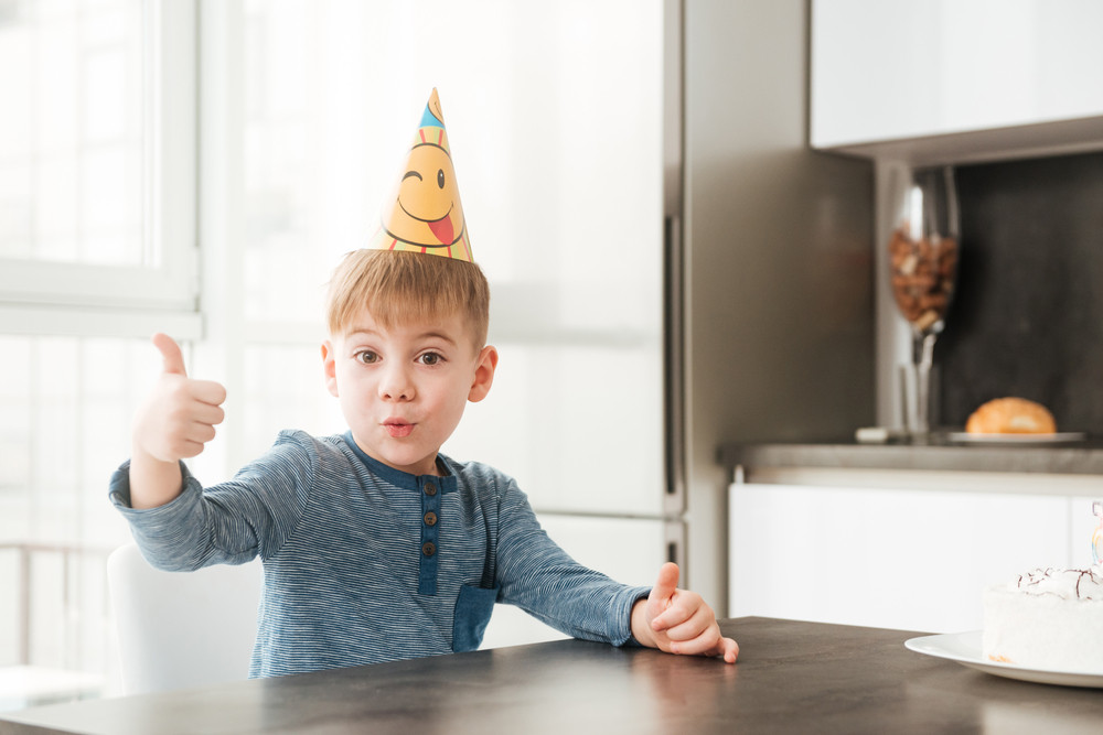 Photo of little happy birthday boy sitting in kitchen while making thumbs up gesture. Look at the camera.