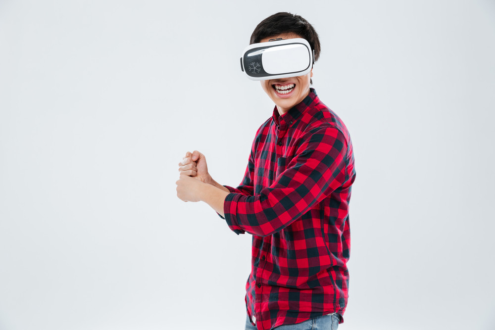 Photo of man dressed in casual shirt in a cage and wearing virtual reality device and holding an imagine tennis racket. Isolated over white background.