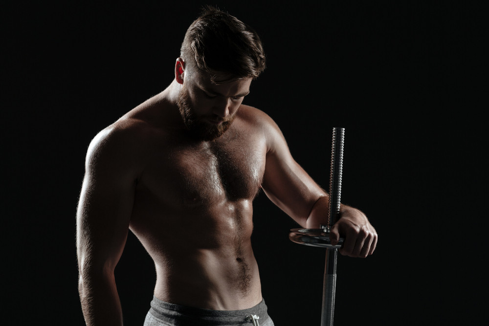 Photo of naked athletic man with barbell. isolated dark background