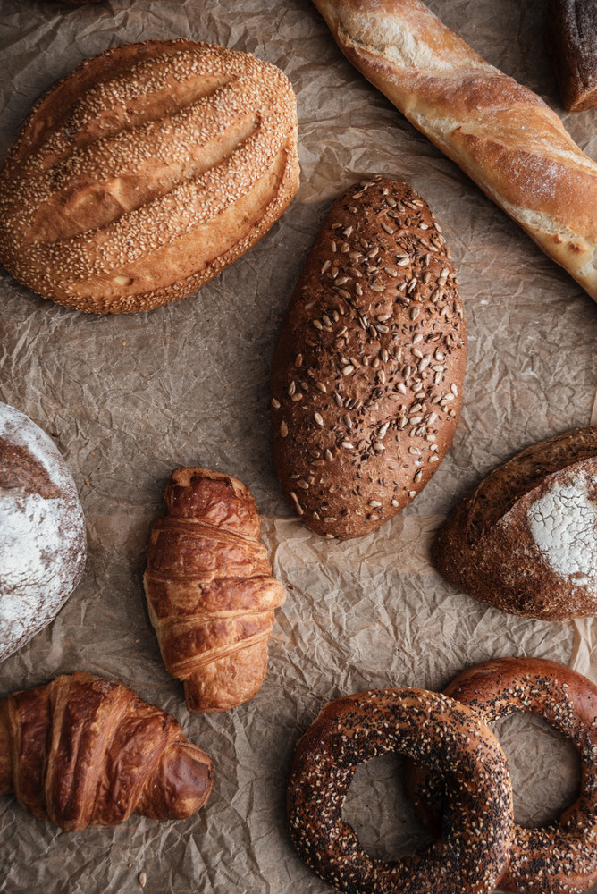 Photo of pastries and bread with flour on table at bakery