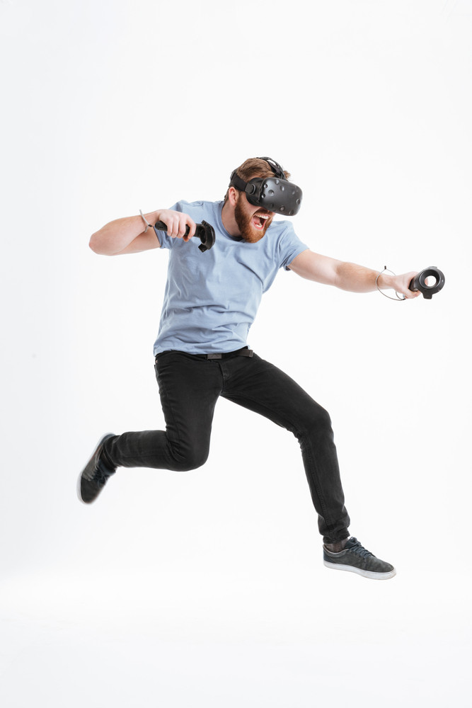 Photo of playful bearded man wearing virtual reality device standing over white background and jumping.
